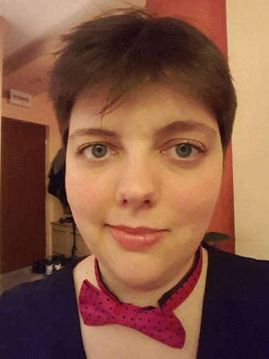 A selfie of Rita gazing at the camera with a half-smile while wearing a pink bowtie with navy blue polka dots and a black top.