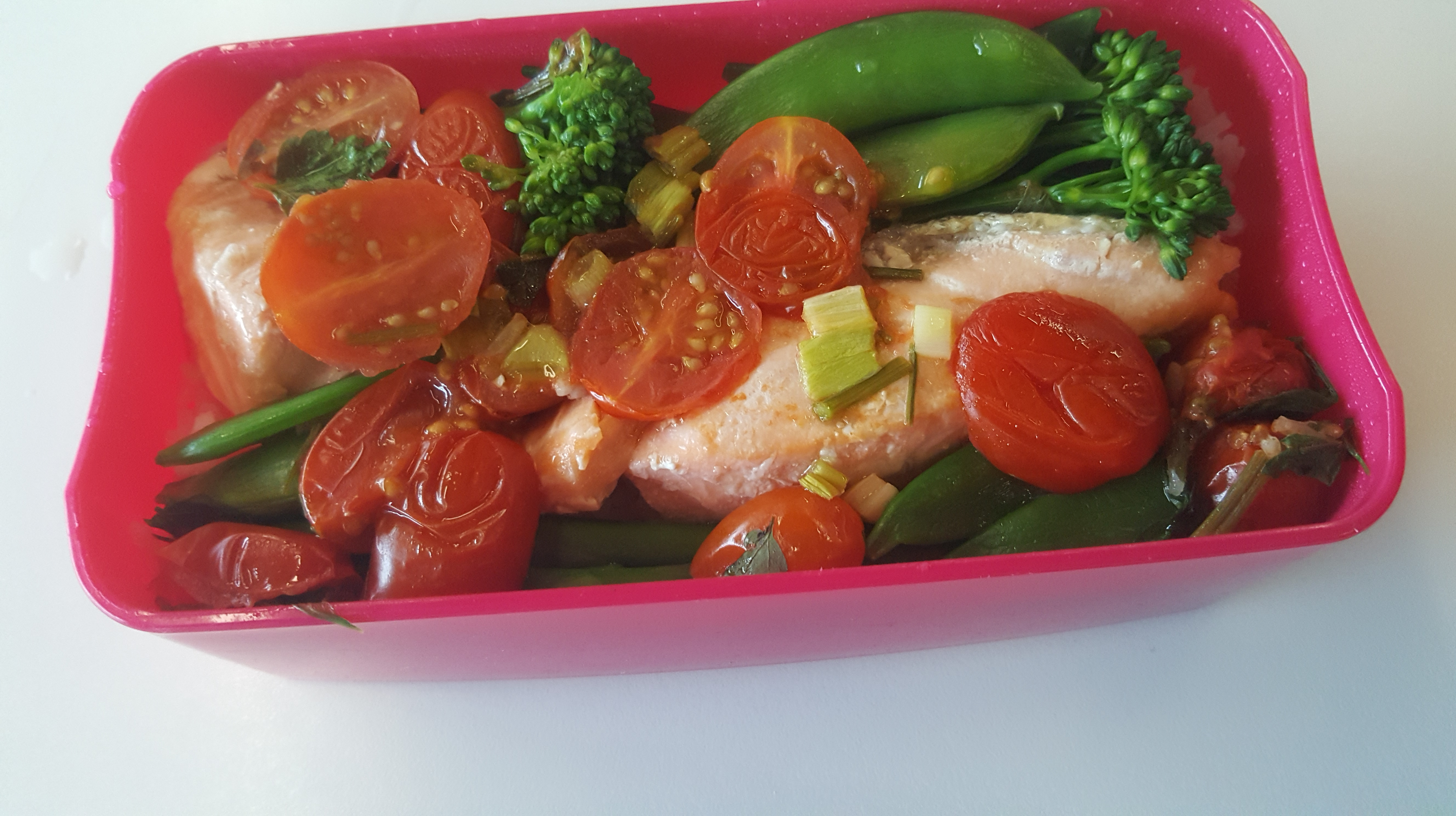 A picture of a lunchbox filled with cooked salmon on bed of rice, with visible sugar snaps, broccoli and cherry tomatoes.