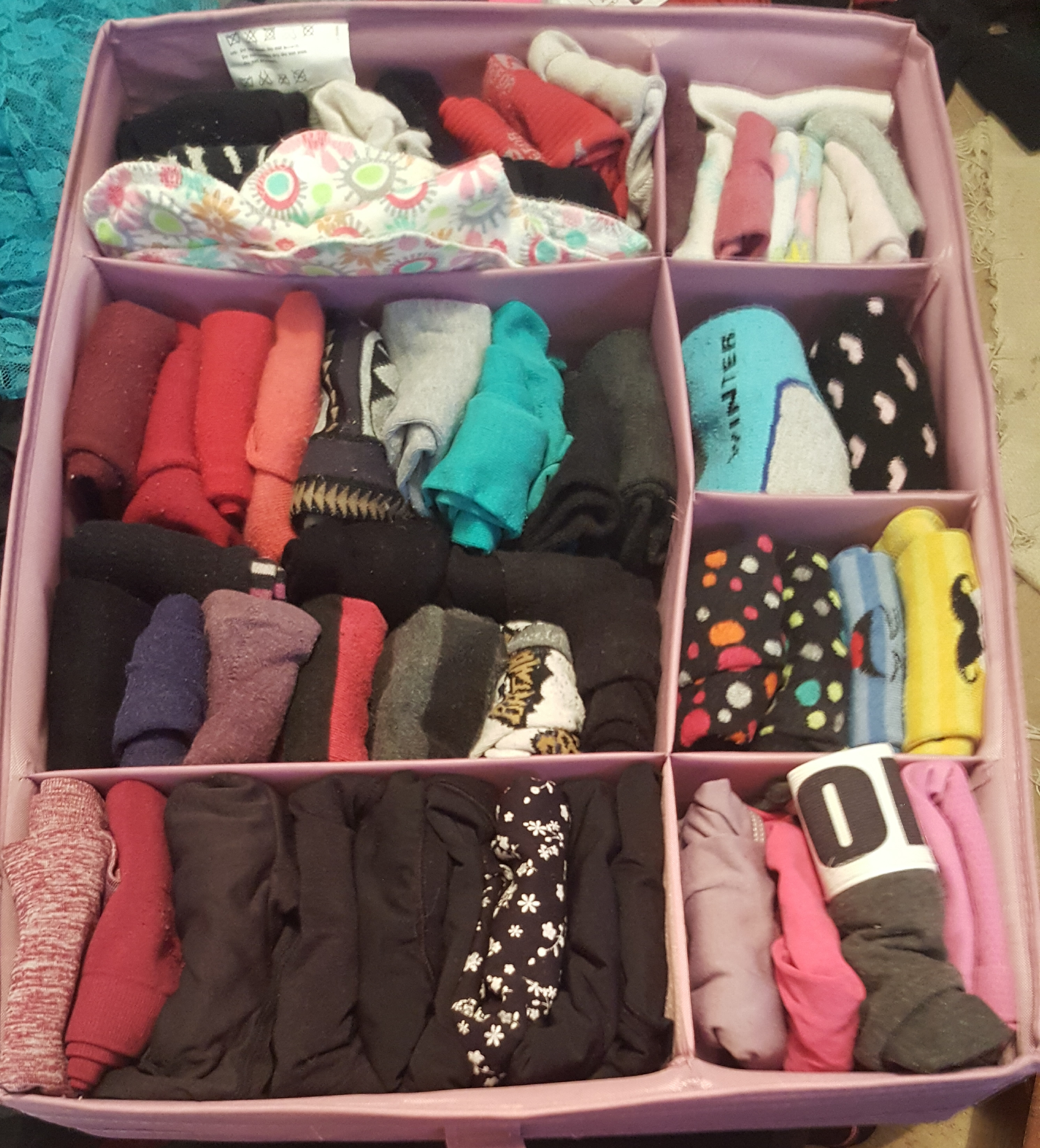 A square Ikea container with dividers, stuffed with socks and underwear, all stored vertically.