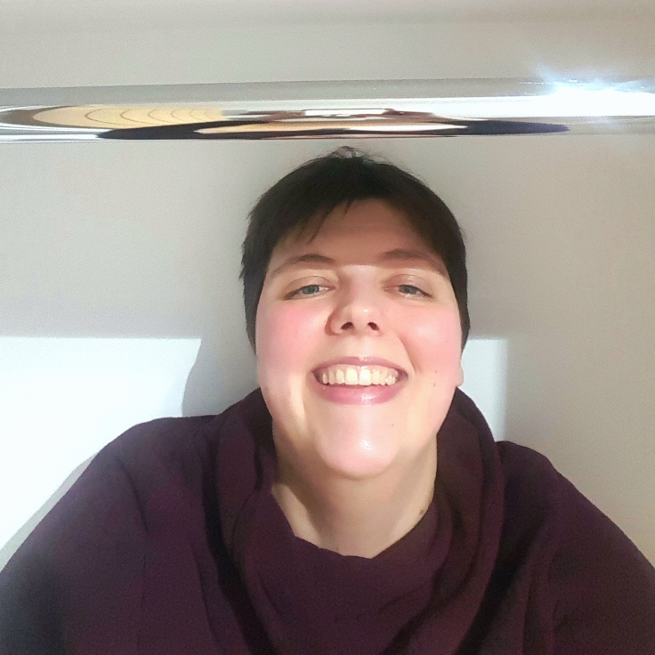 A grinning selfie of Rita wearing a cowlneck sweater standing in a white walk in wardrobe with a steel pole for hangers shining above her.