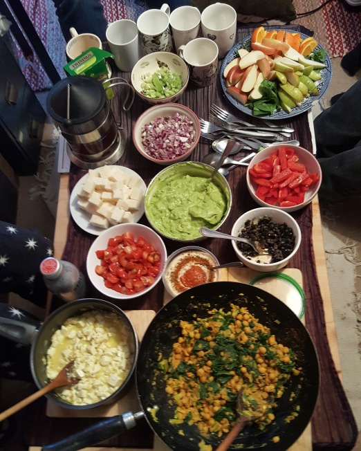A mostly vegan brunch: large frying pan with chickpeas, a smaller one with tofu, also olives, hummus, tomatoes, guacamole, goat cheese (non-vegan), fruit, tea and several mugs. All set on a table with some feet/legs visible around.